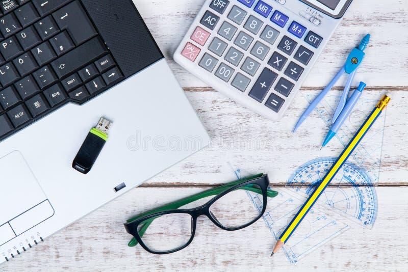 Vista superiore del computer portatile, del calcolatore, dei vetri, della matita, del righello e di USB immagini stock libere da diritti