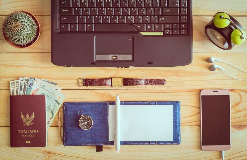 Vista superiore del computer portatile, taccuino, penna, passaporto, soldi, telefono cellulare fotografia stock
