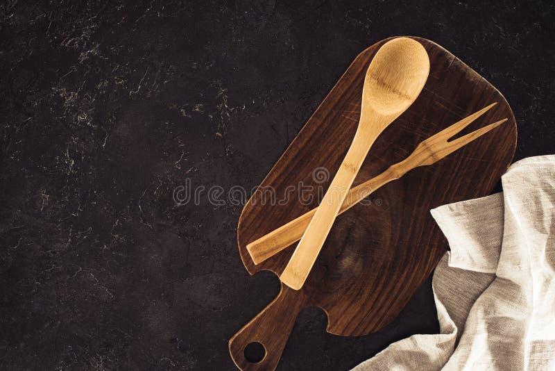 vista superiore del cucchiaio, della forchetta per carne sul tagliere di legno e della tela di sacco immagini stock