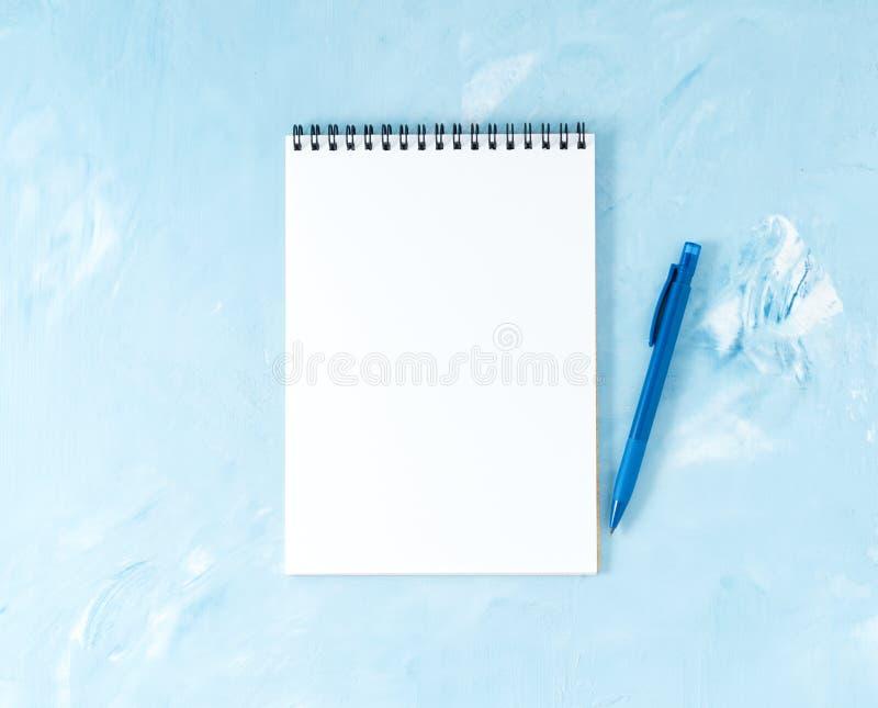 Vista superiore del desktop blu luminoso moderno dell'ufficio con la penna o la matita, blocco note Derisione su, spazio vuoto fotografia stock libera da diritti