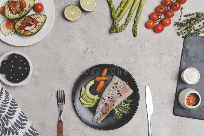vista superiore del filetto di pesce con le carote di bambino sul piatto e verdure sane fresche e frutta fotografia stock libera da diritti