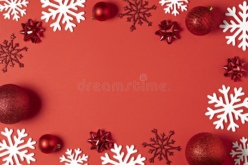 Vista superiore del fondo rosso di Natale Palle del nuovo anno di festa, fiocchi di neve decorativi di natale con la struttura pe fotografia stock libera da diritti