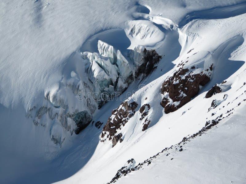 Vista superiore del ghiacciaio e delle scogliere rocciose innevate di sporgenza e delle montagne un giorno soleggiato fotografia stock