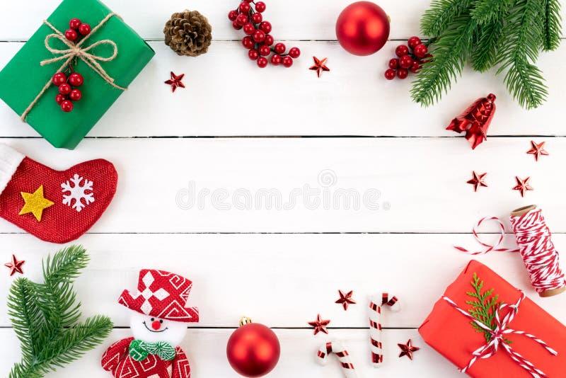 Vista superiore del Natale verde e contenitore di regalo rosso con i rami attillati, le pigne, le bacche rosse e la campana su fo fotografia stock libera da diritti