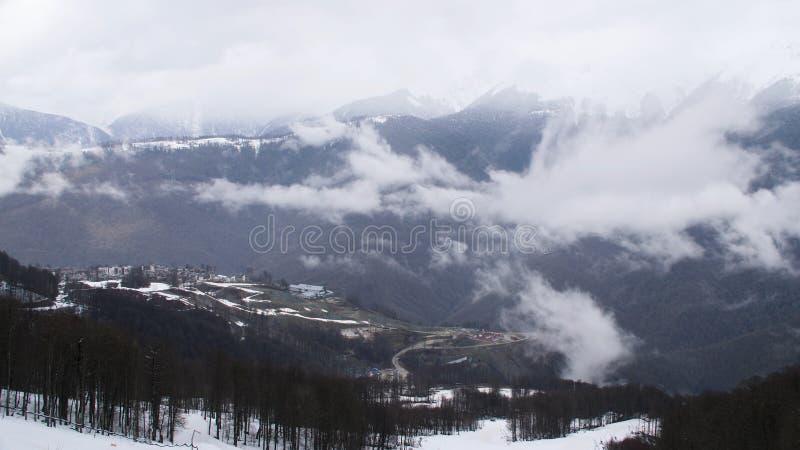 Vista superiore del paesaggio della montagna e di piccola località di soggiorno di inverno Nuvole tristi che tessono sopra i picc immagine stock libera da diritti