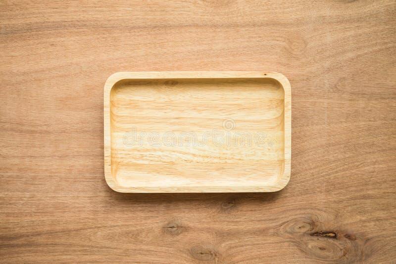 Vista superiore del piatto di legno fatto a mano marrone nuovissimo inutilizzato del piatto sul fondo di legno della tavola fotografie stock