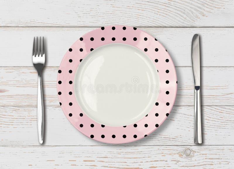 Vista superiore del piatto rosa vuoto del pois sulla tavola di legno immagini stock