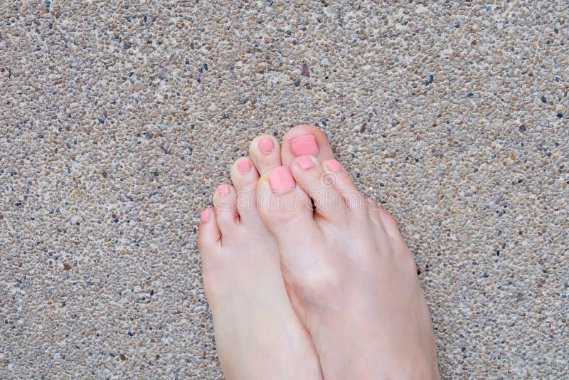 Vista superiore del piede femminile Manicure rosa dello smalto Selfie dei piedi nudi della donna sul fondo della strada immagini stock
