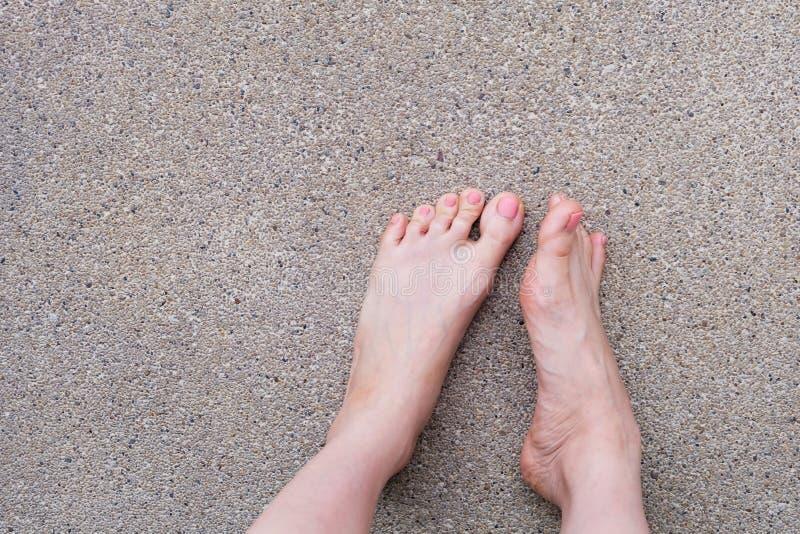 Vista superiore del piede femminile Manicure rosa dello smalto Selfie dei piedi nudi della donna sul fondo della strada fotografie stock