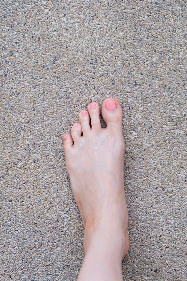 Vista superiore del piede femminile Manicure rosa dello smalto Selfie dei piedi nudi della donna sul fondo della strada immagine stock