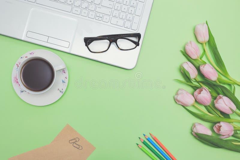 Vista superiore del posto di lavoro del progettista con il computer portatile, i tulipani rosa, la tazza di tè, i vetri, le matit immagine stock libera da diritti