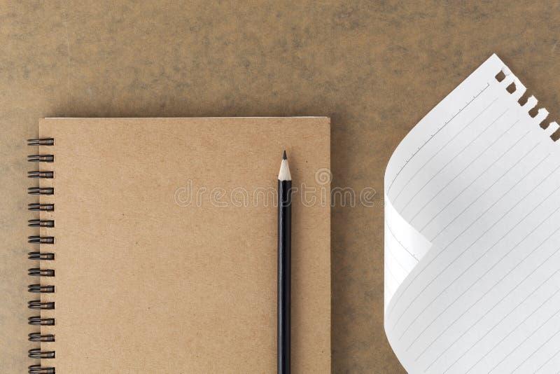Vista superiore del taccuino marrone in bianco della copertina di carta con la matita nera o fotografie stock