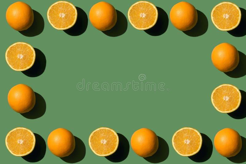 vista superiore del telaio fatta dalle intere ed arance affettate mature fresche immagini stock libere da diritti