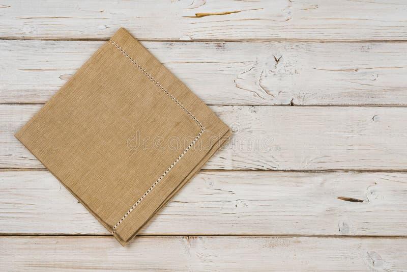 Vista superiore del tovagliolo marrone della cucina sul fondo di legno delle plance fotografia stock