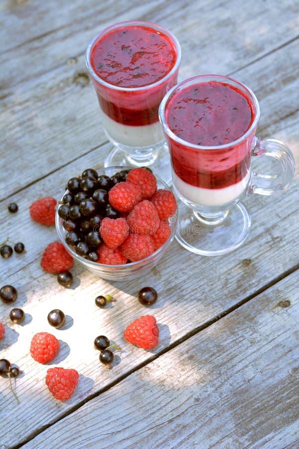 Vista superiore del vaso di vetro in pieno del lampone fragrante e rosso e della mora vicino a yogurt saporito con le bacche mesc fotografie stock libere da diritti