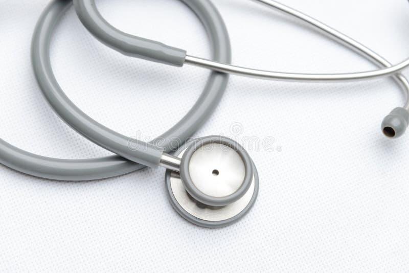 Vista superiore dell'attrezzatura medica grigia dallo stetoscopio su tela bianca dispositivo degli strumenti per medico fotografia stock