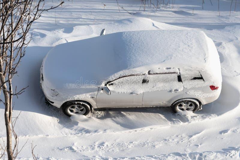 Vista superiore dell'auto bianca parcheggiata in cumulo di neve e coperta di laye fotografia stock libera da diritti