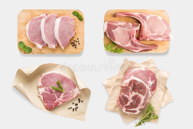 Vista superiore dell'insieme crudo della bistecca di braciola di maiale del modello isolato sul BAC bianco fotografia stock libera da diritti
