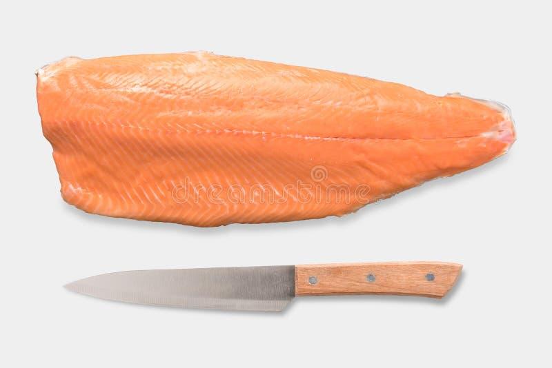 Vista superiore dell'insieme fresco del salmone e del coltello del modello isolato su bianco fotografia stock