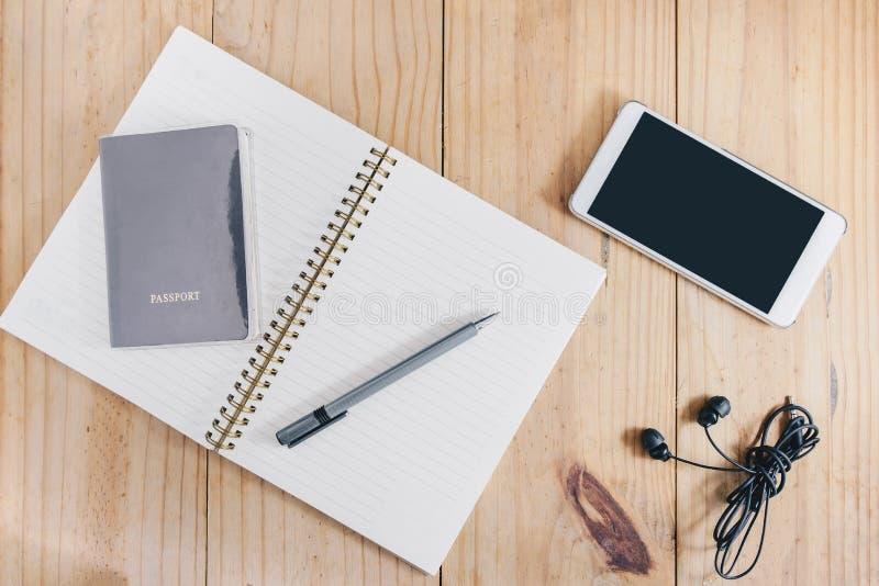 Vista superiore dell'oggetto di viaggio: passaporto e matita grigia sul taccuino bianco, sul telefono cellulare bianco e sul tras fotografia stock