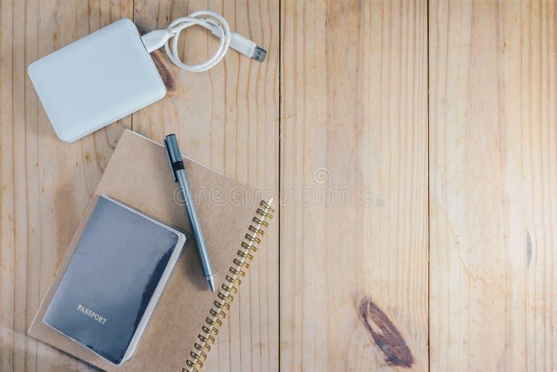 Vista superiore dell'oggetto di viaggio: passaporto e matita grigia sul taccuino marrone e sul disco rigido esterno bianco sulla  fotografia stock