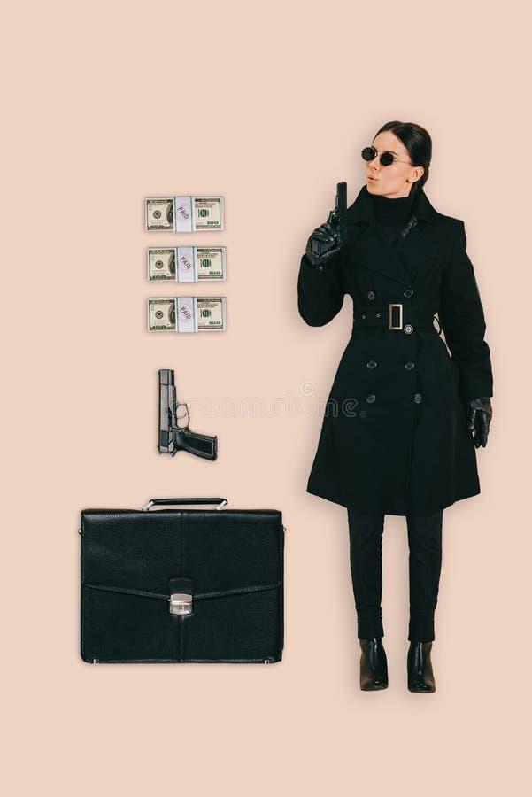vista superiore dell'uccisore femminile in occhiali da sole con le rivoltelle ed i contanti della cartella fotografie stock