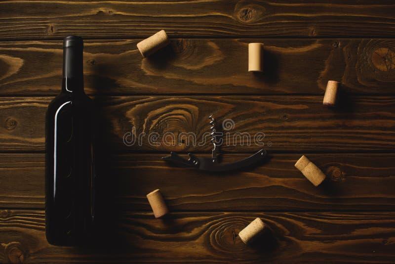 vista superiore della bottiglia di vino rosso con la cavaturaccioli circondata con i sugheri fotografie stock libere da diritti