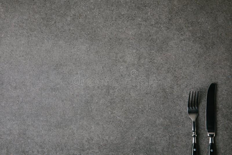 vista superiore della forcella e del coltello brillanti su fondo grigio fotografia stock