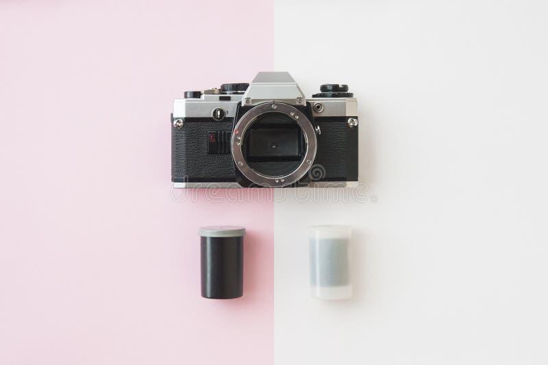 Vista superiore della macchina fotografica di Analaog SLR con le scatole metalliche del film da 35 millimetri sul rosa fotografia stock