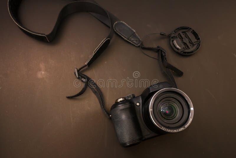 Vista superiore della macchina fotografica digitale con fondo marrone fotografia stock