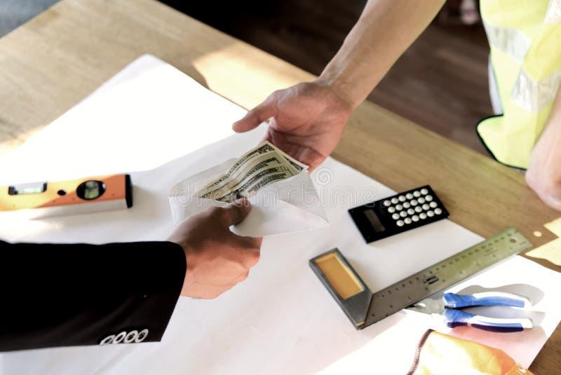 Vista superiore della mano del capo o del proprietario che d? soldi all'impiegato o alla persona impiegata per il suo stipendio o immagine stock