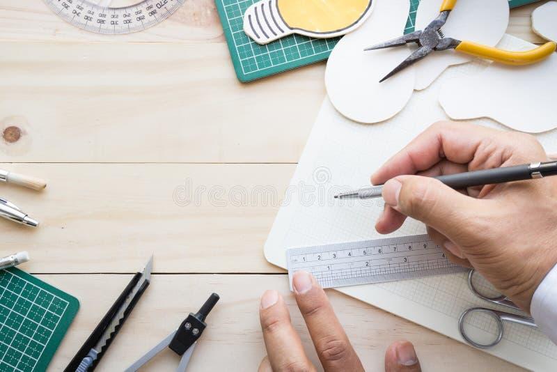 Vista superiore della mano maschio sulla tavola di legno con gli elementi degli strumenti fotografie stock libere da diritti