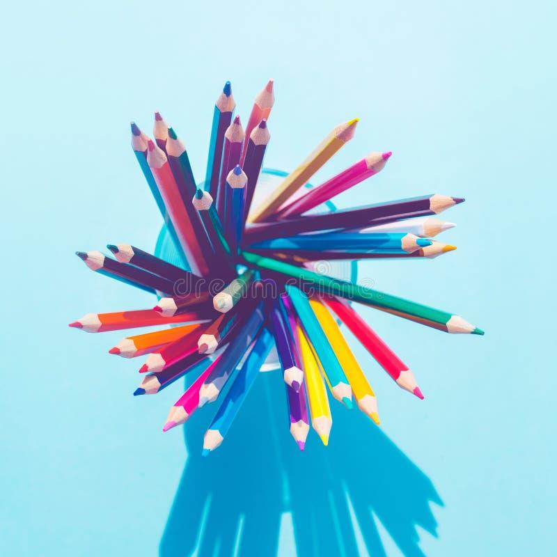 Vista superiore della matita variopinta in vetro con ombra lunga su fondo pastello immagine stock libera da diritti