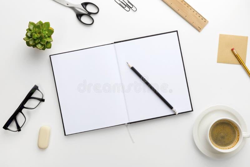 Vista superiore della scrivania bianca con il taccuino ed i rifornimenti fotografie stock