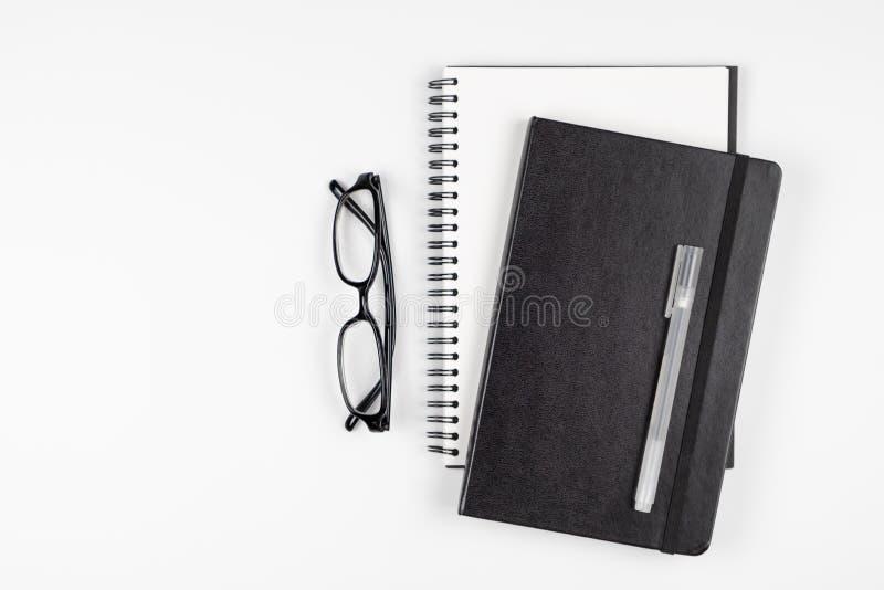 Vista superiore della scrivania con la penna e gli occhiali dei taccuini fotografia stock