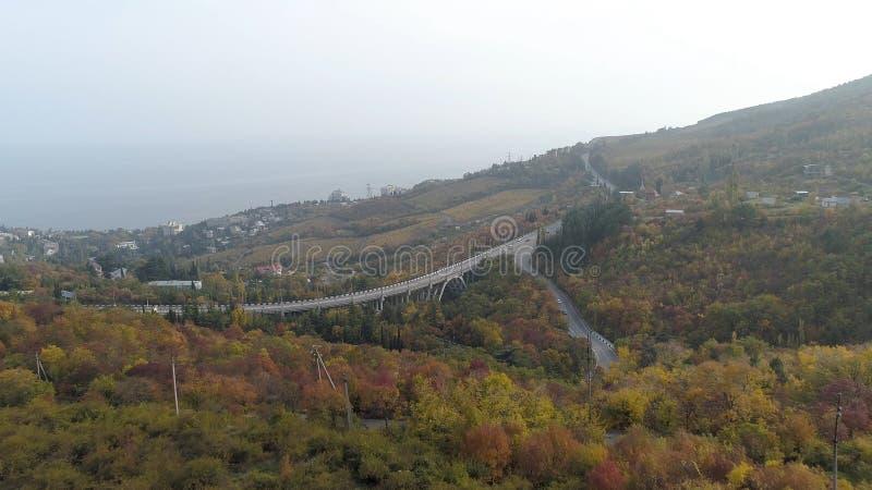 Vista superiore della strada principale nella foresta di autunno sulla collina colpo Panorama della città sulla costa vicino alla immagine stock