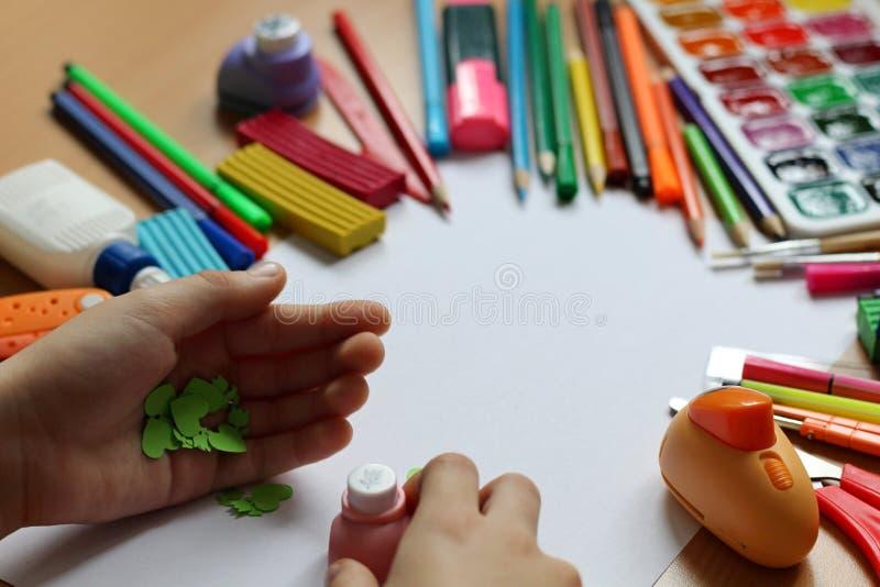 Vista superiore della tavola con un foglio di carta pulito le mani di un bambino e che fanno un regalo Festa della mamma ed il gi fotografie stock libere da diritti