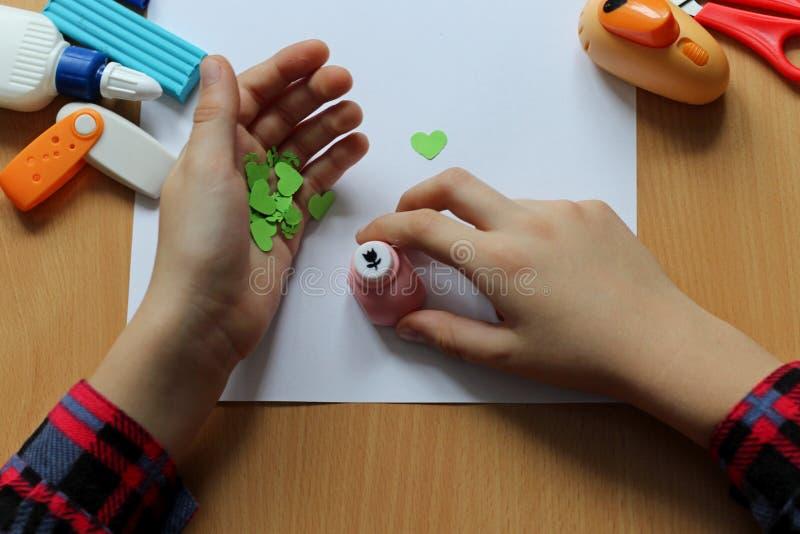 Vista superiore della tavola con un foglio di carta pulito le mani di un bambino e che fanno un regalo Festa della mamma ed il gi fotografia stock