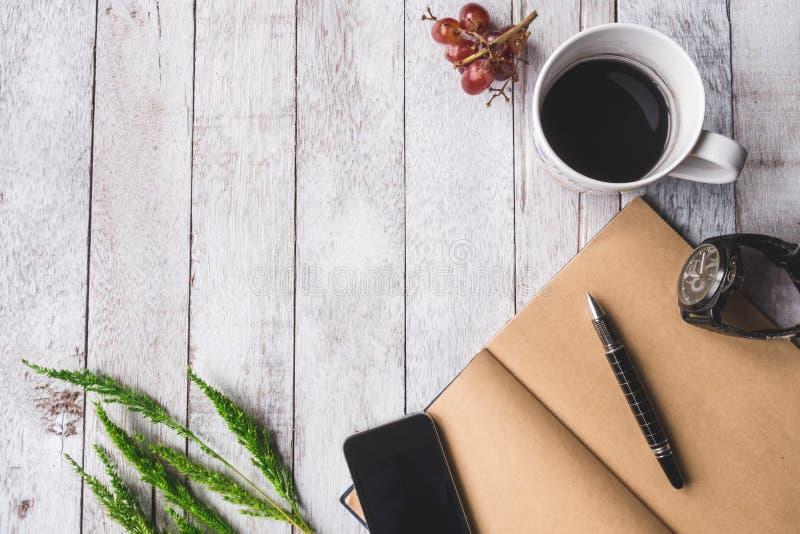 Vista superiore della tazza di caffè con il taccuino in bianco, penna, uva, orologio immagine stock libera da diritti