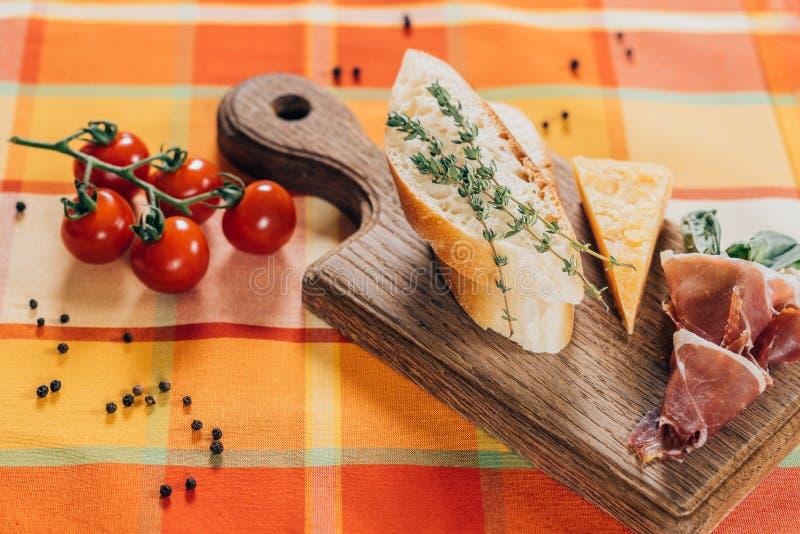 vista superiore delle baguette, della carne e del parmigiano affettati sul tagliere di legno e sui pomodori ciliegia freschi fotografia stock