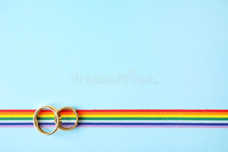 Vista superiore delle fedi nuziali e del nastro dell'arcobaleno, spazio per testo Simbolo gaio fotografia stock