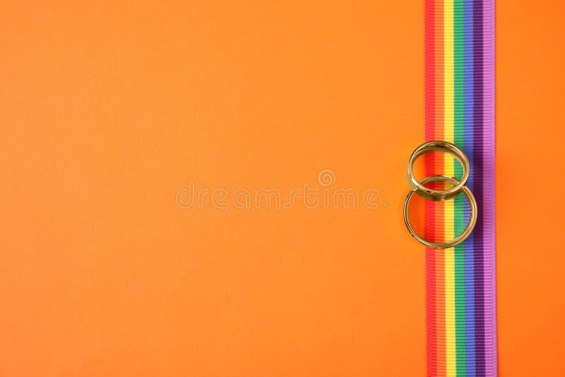 Vista superiore delle fedi nuziali e del nastro dell'arcobaleno sul fondo di colore Simbolo gaio fotografia stock