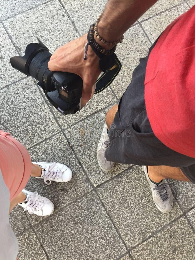 Vista superiore delle gambe degli uomini e femminili e mani degli uomini che tengono una macchina fotografica di DSLR immagine stock