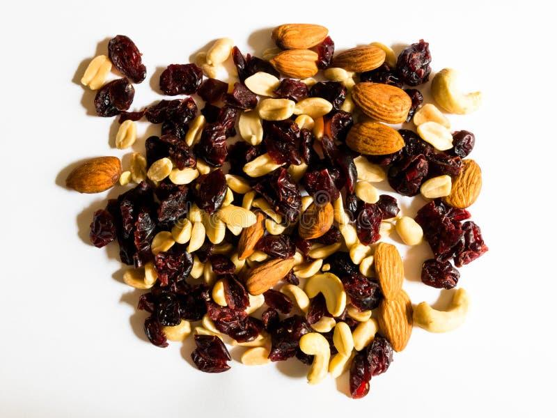 Vista superiore delle mandorle, delle arachidi, degli anacardi e dei mirtilli rossi secchi su fondo bianco fotografia stock libera da diritti