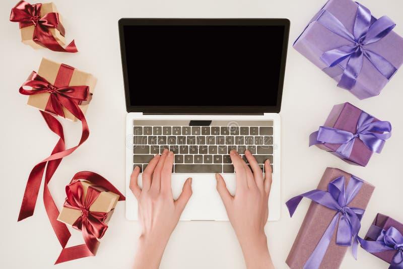 Vista superiore delle mani della donna di affari sul computer portatile fra i contenitori di regalo fotografia stock libera da diritti