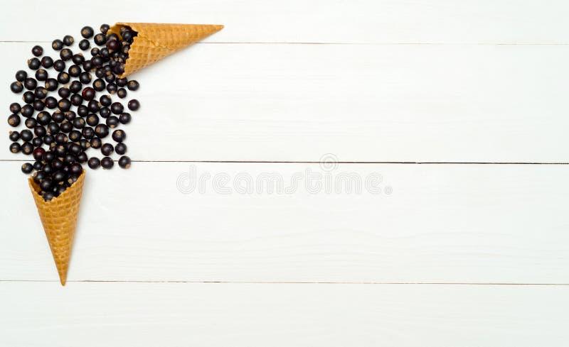 Vista superiore delle more organiche fresche dolci nel cono della cialda, spazio libero Bacche fresche in cono su fondo di legno  fotografia stock libera da diritti