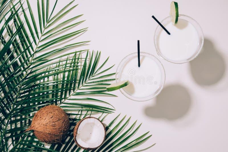 vista superiore delle noci di cocco organiche, delle foglie di palma verdi e dei cocktail della noce di cocco in vetri con le can fotografia stock libera da diritti