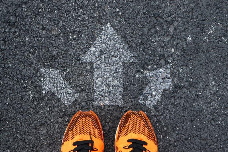 Vista superiore delle scarpe di sport sulla strada con le frecce immagine stock libera da diritti