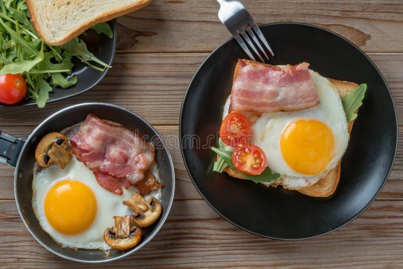 Vista superiore delle uova fritte sulla banda nera e sulla pentola con la forcella, i funghi e il rukkola fotografia stock