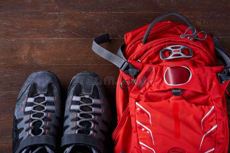 Vista superiore dello zaino turistico e delle scarpe allegre sui bordi di legno immagine stock